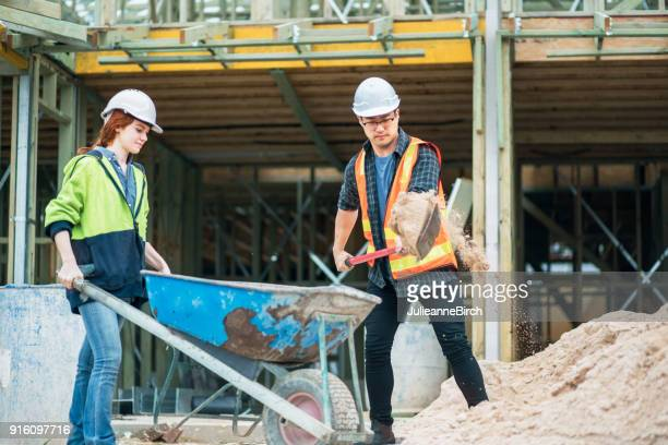 shovelling sand on building site, man and woman builders - wheelbarrow stock photos and pictures