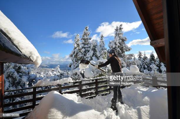 shovelling snow in bariloche, argentina - radicella stock photos and pictures