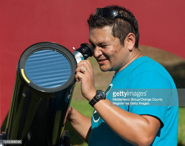 Shovit Bhari a staf physicist in the College of Natural Sciences and Mathematics looks through a telescope to view the partial solar eclipse...