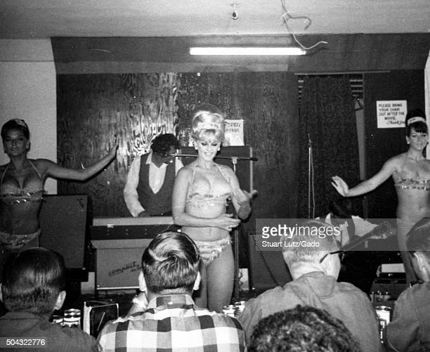 USO Show American soldiers viewed from behind watching three woman in revealing bikinis dance seductively during a show in Vietnam during the Vietnam...