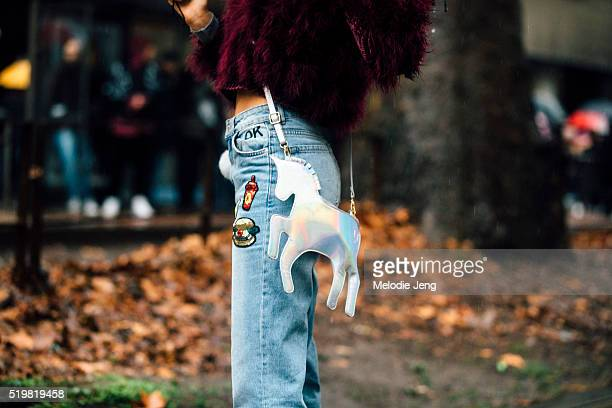 A show attendee wears highwasted jeans with sequin soda and hamburger patches and a silver unicorn purse at the Dolce Gabbana show at Metropol during...