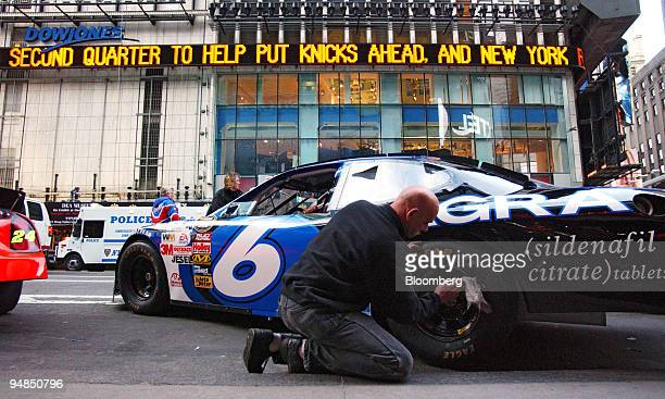 Show Car hauler Paul Jackson cleans the tire of a NASCAR show car outside the NASDAQ Marketsite in the Times Square area of New York Thursday...