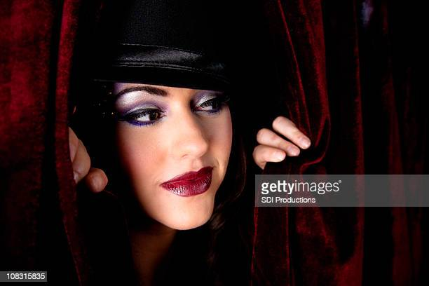 show girl looking through dark red curtain - showgirl stock pictures, royalty-free photos & images