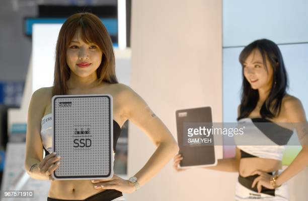 Show girls demonstrate placards showing the latest SSD technology during Computex 2018 at the Nangang Exhibition Center in Taipei on June 5 2018