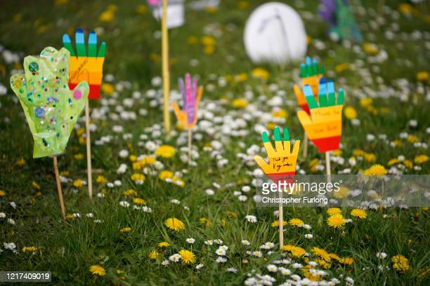 A show of rainbow coloured hands made by local children in support of keyworkers and the NHS adorns a grass verge covered in Spring flowers on April...