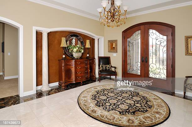 showcase home interior, front door, persian rug, entry foyer, chandelier - persian rug stock photos and pictures