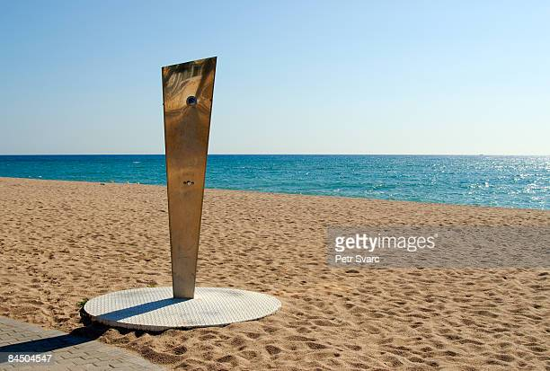 shower on empty beach, spain - maresme stock photos and pictures