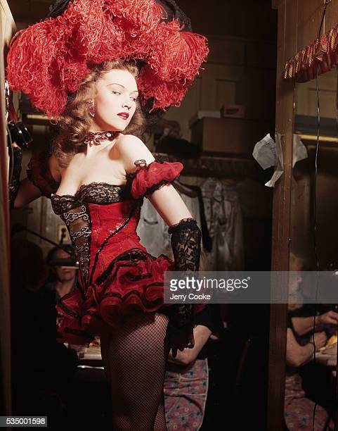 A showgirl checks the fit of her costume in the dressing room before taking the stage She works for the Latin Quarter Nightclub