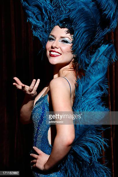 Showgirl on dark stage wearing a outfit made of feathers