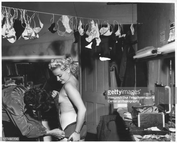 A showgirl strategically holds up her costume as an assistant unzips it for her in a dressing room mid 20th century Photo by Weegee/International...