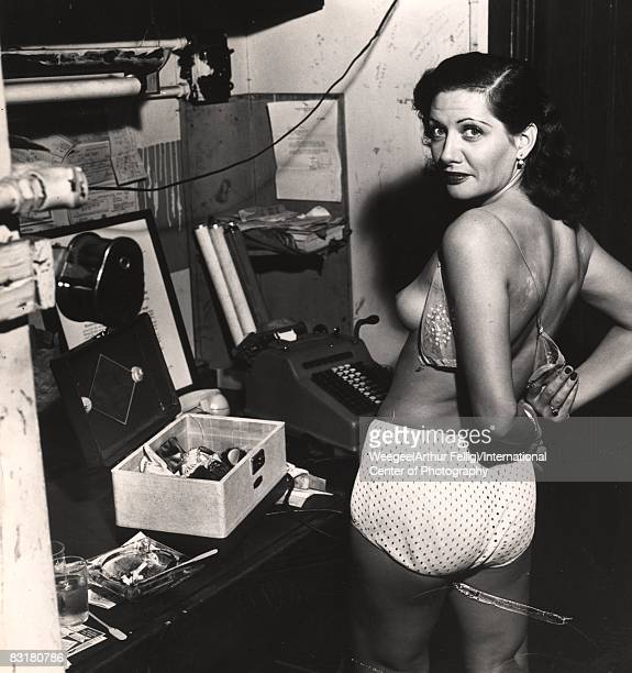 A showgirl turns around while getting dressed in a backstage dressing room New York ca1950s Photo by Weegee/International Center of Photography/Getty...