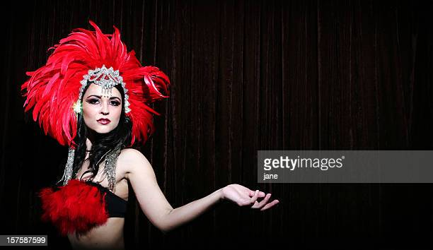 Showgirl with red feather headdress on black background