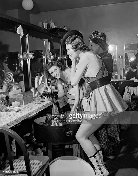 Showgirls get ready for a show in the dressing room of Radio City Music Hall The three girls are seen together trying on bonnets