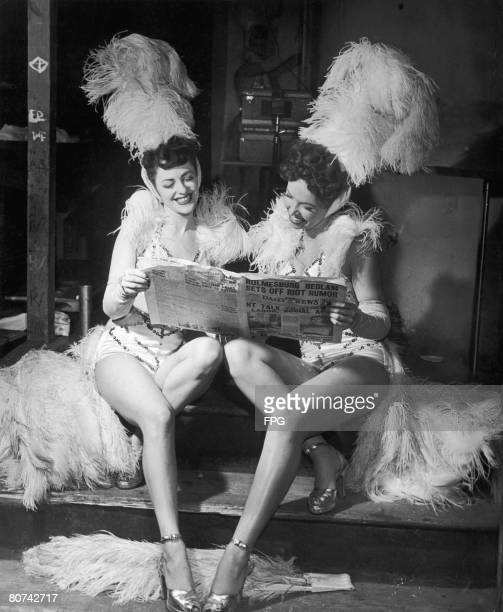 Showgirls Marion Swoyer and Mitze Mann read the Philadelphia Daily News between their turns on stage 1949