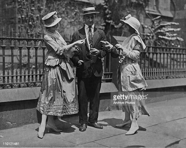 Showgirls selling tickets to a man in the street circa 1925