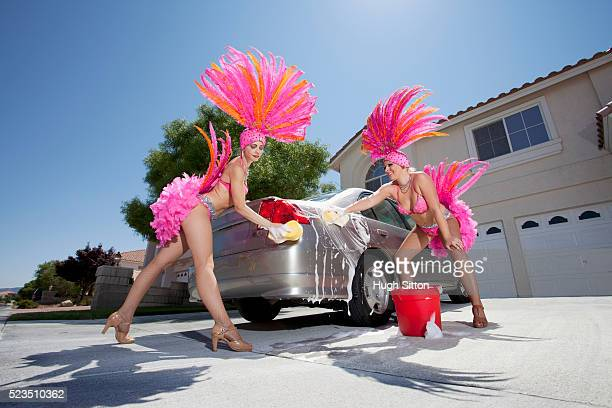 Showgirls washing car outside house