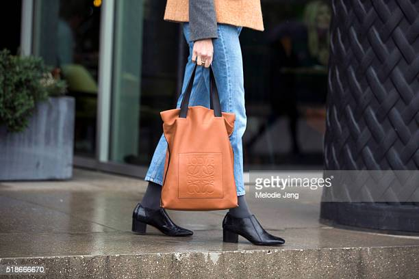 A showgoer carries an orange Loewe logo tote bag during London Fashion Week Autumn/Winter 2016/17 at the Anya Hindmarch show at Kings Cross on...