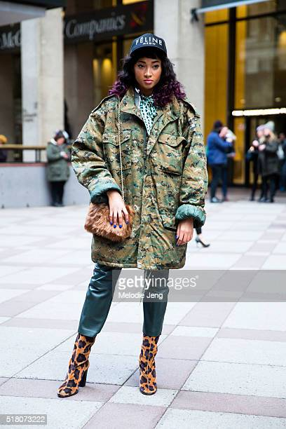 A showgoer outside the Yeezy show at Madison Square Garden wears a 'Feline Meow' cap has dyed purple ombre curly hair wears a green...