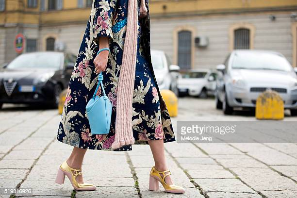 A showgoer wear san embroidered floral coat blue purse and pink and gold heels at the Gucci show during the Milan Fashion Week Fall/Winter 2016/17 on...