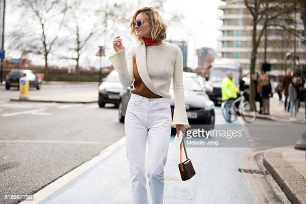 A showgoer wears a chunky clear frame sunglasses asymmetrical tan and orange top white jeans a red bandana around her neck and a Louis Vuitton...