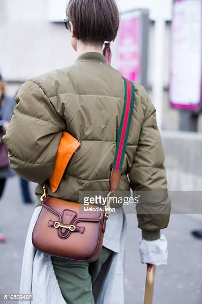 A showgoer wears a green puffer jacket with a leather Gucci purse at the Ellery show at Palais de Tokyo on March 07 2016 in Paris France