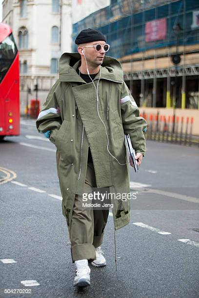 A showgoer wears a large olive Juun J parka and Raf Simons x Adidas sneakers during The London Collections Men AW16 at Victoria House on January 9...