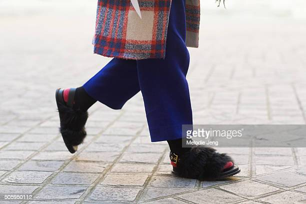 A showgoer wears black chunky furry sandals with a back belt over red socks on January 20 2016 in Paris France