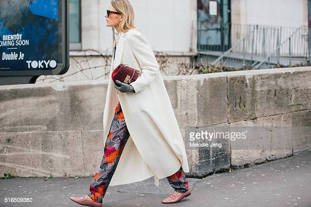 A showgoer wears Celine sunglasses a white coat a red Chloe purse floral Gucci trousers and pink Gucci loafers at the Ellery show at Palais de Tokyo...
