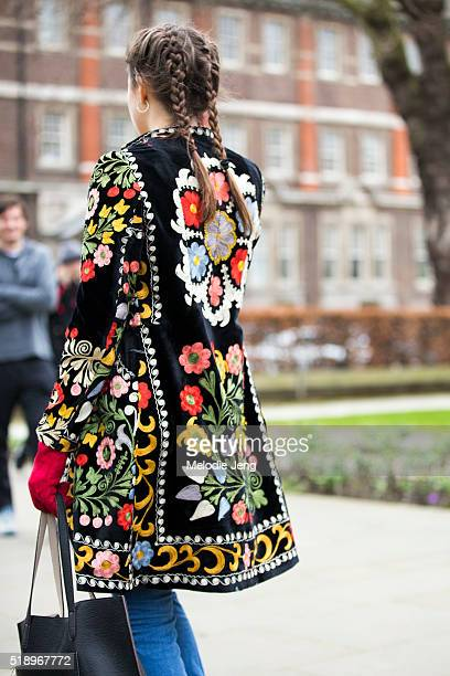A showgoer wears her hair in two french braids and wears a floral embroidered jacket at the Topshop show at Tate Britain during London Fashion Week...