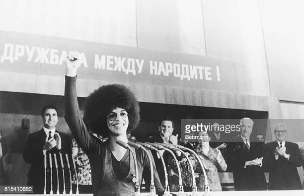 Showing a Black Power salute and that now familiar gap-toothed smile. Black American militant, Angela Davis, earns warm applause from her audience in...