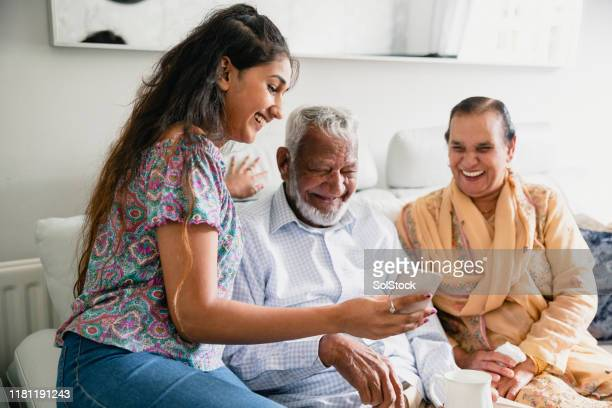 showing grandparents phone - indian ethnicity stock pictures, royalty-free photos & images