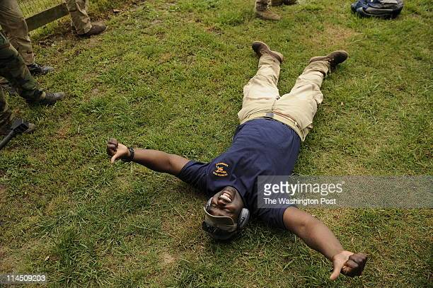 Showing his enjoyment Darion Brown of California lays on the ground after firing a 50 caliber sniper rifle while taking part in the Extreme SEAL...