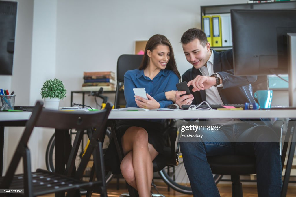 Showing photos to a colleague at work : Stock Photo