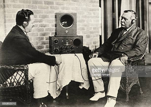 Showing Sir Arthur Conan Doyle at right and FD Waller vice president of the John Firth Company Radio Corporation of New York listening to a concert...