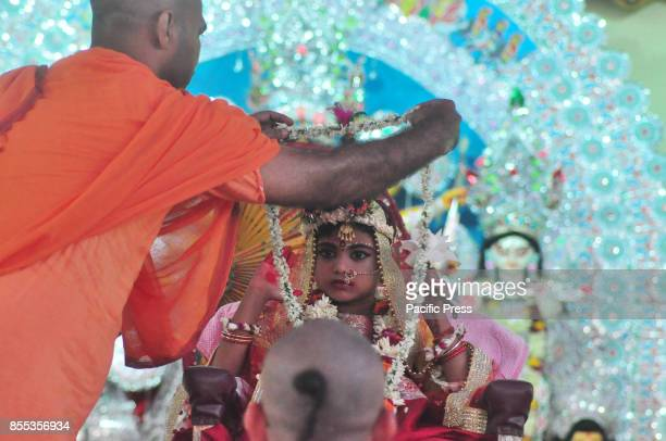 Showlina Banerjee age 4 years 10 month and 19 days dressed as a Kumari yawns while she is worshiped by a Hindu priest during the religious festival...