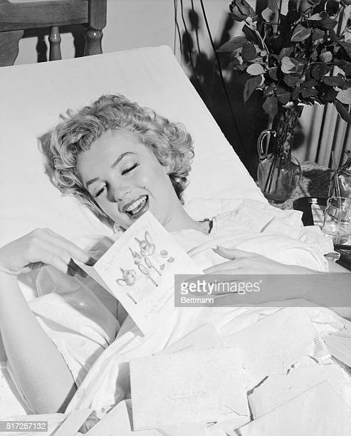 Shown here recovering from a recent operation for an appendectomy is glamorous motion picture actress Marilyn Monroe as she reads a Getwell Card from...