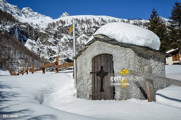 Shown in this picture is a tool shed covered with abundant snow during a clear day; the location is Vaud hamlet, located in Ollomont, Italian Alps.