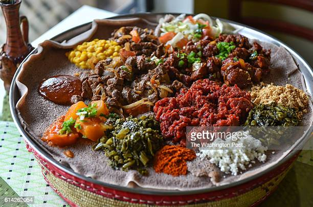 Shown is a family style serving of Lamb Tibs center left Gored Gored center right and Kitfo center bottom surrounded by sides of cottage cheese...