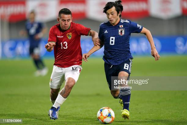 Shoya Nakajima of Japan and Henry Vaca of Bolivia compete for the ball during the international friendly match between Japan and Bolivia at Noevir...
