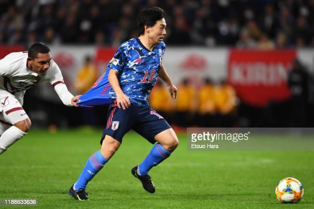 Shoya Nakajima of Japan and Bernaldo Manzano of Venezuela compete for the ball during the international friendly match between Japan and Venezuela at...