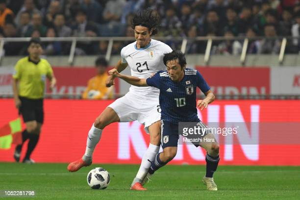Shoya Nakajima of Japan and Edinson Cavani of Uruguay compete for the ball during the international friendly match between Japan and Uruguay at...