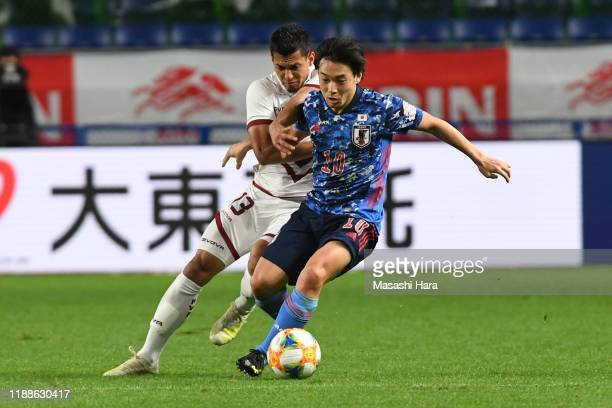 Shoya Nakajima of Japan and Renzo Zambrano of Venezuela compete for the ball during the international friendly match between Japan and Venezuela at...