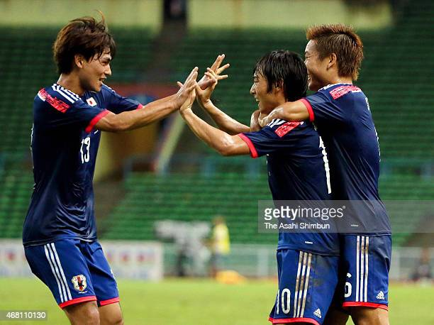 Shoya Nakajima of Japan celebrates scoring his team's first goal with his team mates Takumi Minamino and Ryosuke Yamanaka during the AFC U23...
