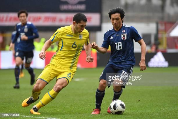 Shoya Nakajima of Japan keeps the ball the ball under the pressure from Taras Stepanenko of Ukraine at Stade Maurice Dufrasne on March 27 2018 in...