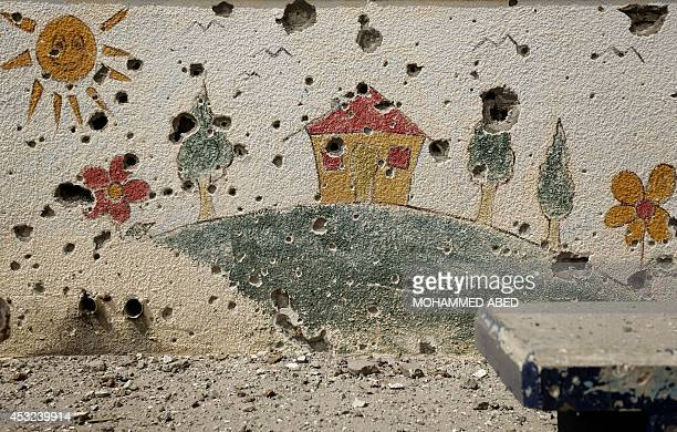 Shrapnel holes are seen on a decorated wall in the heavily damaged Sobhi Abu Karsh school in Gaza City's alShejaea neighborhood on August 5 as a...