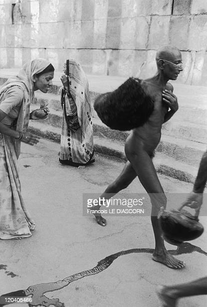 Shravanabelagola India in 2006 Naked Jain monk walking in the road in front of women who are bowing down before him at Karnakata during the ceremony...