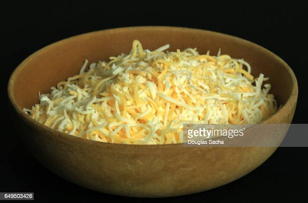 Shredded cheese in a woodeden bowl