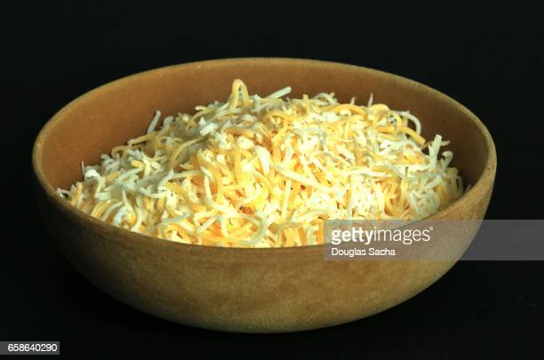 Shredded cheese in a wooden bowl