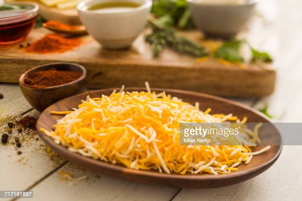 Shredded cheese on wooden plate