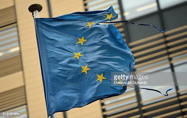 A shredded European Union flag flutters in the wind on March 1 2016 in Brussels / AFP / EMMANUEL DUNAND